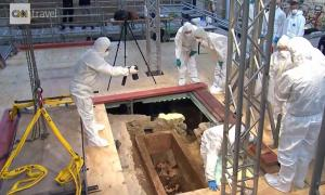 Scientists examining the inside of a 1,000-year-old sarcophagus in Mainz, Germany, after lifting the lid. Source: Print screen, CNN video.