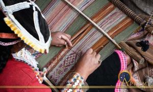 This woman is showing how local textiles are woven.