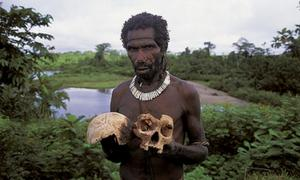 A Fore tribesman of Papua New Guinea holding a skull