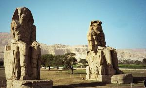 The twin seated Colossi of Memnon, statues of Amenhotep III, on the west back of Luxor, Egypt