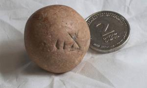 The ancient two-shekel weight, recently found near the Western Wall in Jerusalem, next to a modern Israeli two-shekel coin.  Source: Shai Halevi / Israel Antiquities Authority