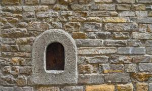 A wine window (buchetta del vino), used in the past to sell wine directly to passers-by, on the old stone wall of an ancient building in the historic centre of Florence, Tuscany, Italy. Source: Simona Sirio /Adobe Stock