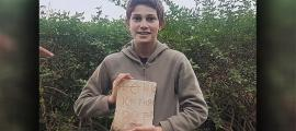 Stav Meir, holding the 1,500-year-old Byzantine inscription that he discovered near Caesarea.	Source: Karem Said/ Israel Antiquities Authority