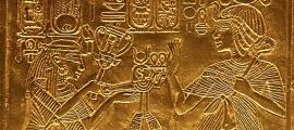Scene from gilded shrine of Tutankhamen showing him and his wife Queen Ankhesenamun. Queen hols a sistrum and menat.