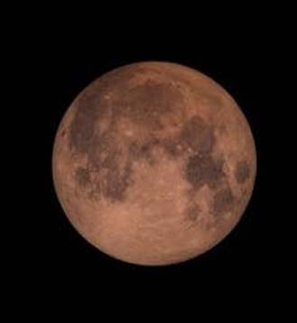 A super blood moon tinted red by scattered light.