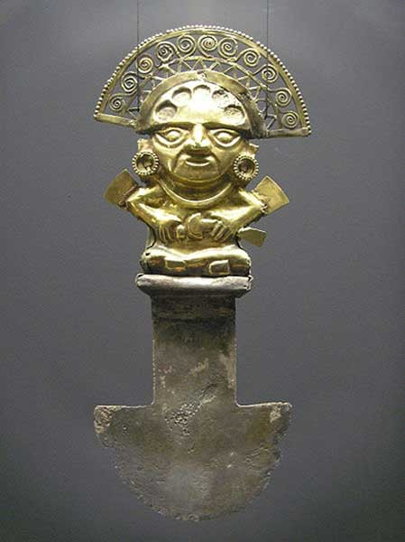 A tumi from Sipán, Peru. 850-1050 AD. The golden effigy depicts a richly decorated dignitary, possibly a priest, who is also holding a sacrificial knife in his hand. The earlobes once had turquoise inlaid in them. The back of this tumi is decorated with tear-shaped gold leaf.