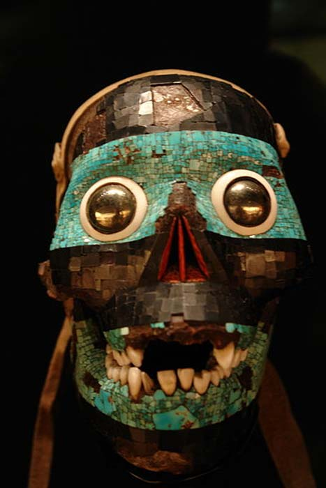 A turquoise mask representing the god Tezcatlipoca (one of the Aztec creator gods). The base for this mask is a human skull. Note the reflective eyes. Mixtec-Aztec. 1400-1521.