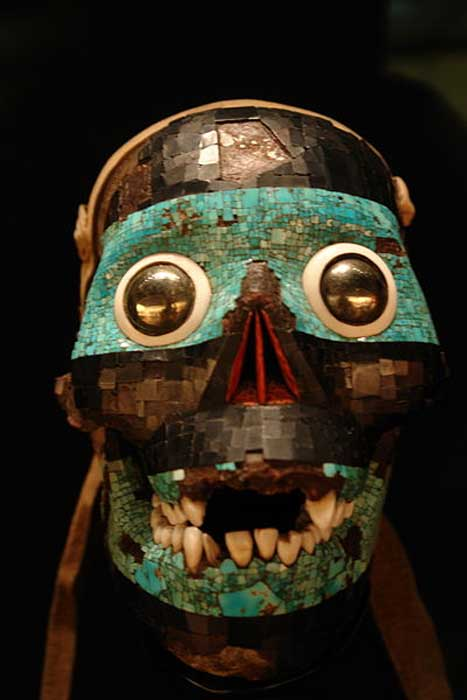 A turquoise mask representing the god Tezcatlipoca. The base for this mask is a human skull. Mixtec-Aztec (1400-1521).