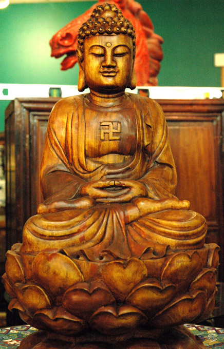 A wooden Buddha in meditation position on lotus flower.